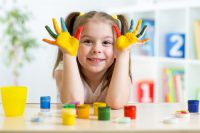 Nursery age pupil experimenting with paint