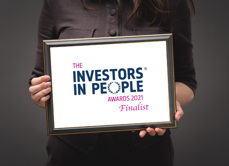 """A person is holding a frame with an image that says: """"THE INVESTORS IN PEOPLE AWARDS 2021 Finalist"""""""